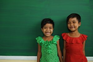 """6-year-old Lae Lae Aung (in green) and 6-year-old May Tha Zin standing in front of a brand-new writing board. Their new school has only just been constructed and everyone in the community is very excited about the handover to take place in the coming months. Asked what they have lost to Nargis, both girls reply simultaneously, """"one pig!."""" Working with local partners, Plan has built and renovated 51 schools and handed them over to local authorities, benefiting thousands of children. Fourteen of the new schools are disaster resilient and can act as emergency shelters."""