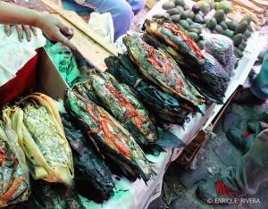 Vendedora muestra los Tlapiques abiertos, abajo se ven los envoltorios de hoja de maíz tatemada (Morelos).